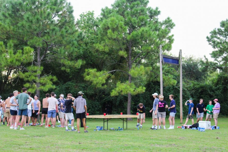 College students mingle while playing a drinking game at The Fly on Sept. 4. Tom Petty & The Heartbreakers song Mary Janes Last Dance plays from a nearby portable speaker as they chat.