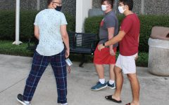 Loyola students Bryan Grassia, Dominic Howell and Adrien Kays walk outside Biever Hall while wearing masks. Wearing masks in public spaces helps to prevent and reduce the spread of COVID-19. Photo credit: Kadalena Housley
