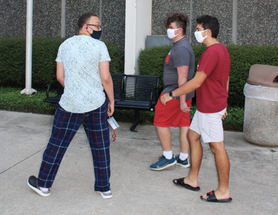 Loyola+students+Bryan+Grassia%2C+Dominic+Howell+and+Adrien+Kays+walk+outside+Biever+Hall+while+wearing+masks.+Wearing+masks+in+public+spaces+helps+to+prevent+and+reduce+the+spread+of+COVID-19.+Photo+credit%3A+Kadalena+Housley