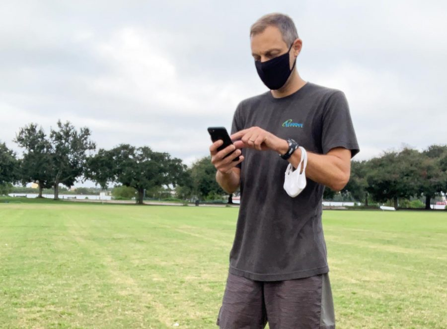 Wolf Pack head cross country coach Geoff Masanet checks his phone at practice. Loyola coaches have had to recruit entirely virtually this year. Photo credit: Jae Schifano