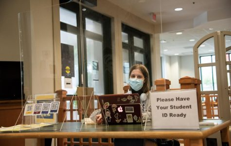Junior Mary Larson sits at the Monroe Library check-in desk as a student worker in the work study program. Due to COVID-19, the options for work study jobs have changed. Photo credit: Michael Bauer