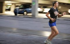 A member of the cross country team runs at an early morning practice Sept. 1. The team has been running in small groups in order to abide by COVID-19 safety guidelines. Photo credit: Peter Buffo