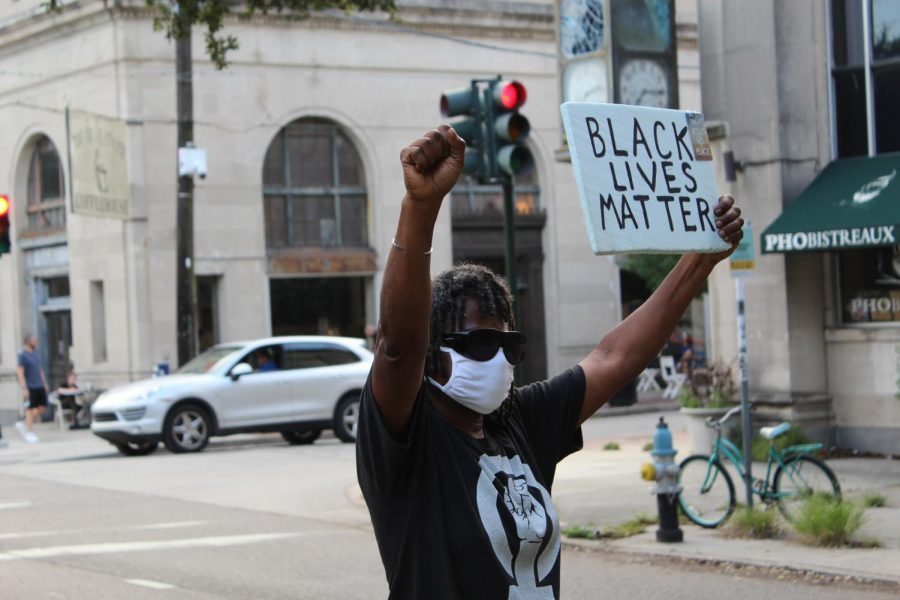 A Protestor on South Carrolton holds up a Black lives matter sign.