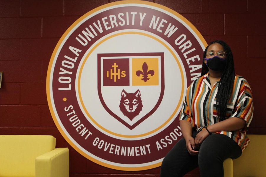 Brionna Wilcher-Hudson takes a seat next to a decorative seal inside Loyola's