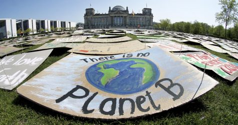 "In this April 24, 2020, file photo, activists place thousands of protest placards in front of the Reichstag building, home of the German federal parliament, Bundestag, during a protest rally of the ""Fridays for Future"" movement in Berlin, Germany. Ten cities around the world, including Berlin, on Tuesday, Sept. 22, 2020, joined New York and London in committing to divest from fossil fuel companies as part of efforts to combat climate change. (AP Photo/Michael Sohn, File)"