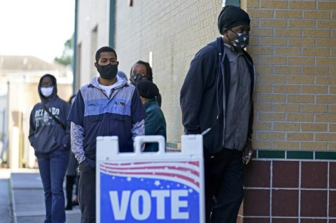 People line up to vote on Election Day at the Matin Luther King, Jr. Elementary School, in the Lower Ninth Ward of New Orleans, Tuesday, Nov. 3, 2020. (AP Photo/Gerald Herbert)