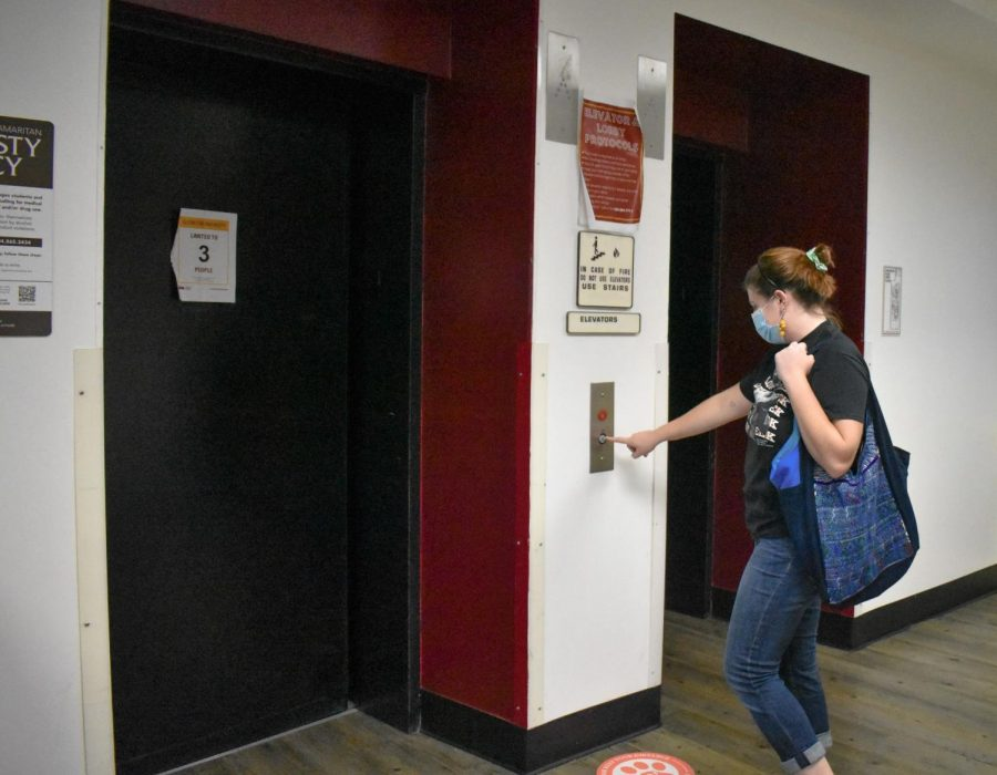 A student calls the elevator in Carrollton Hall. Residential Life plans to fine students living in Carrollton Hall $5 for elevator damage that they believe to be caused by students living there. Photo credit: Maria Paula Marino