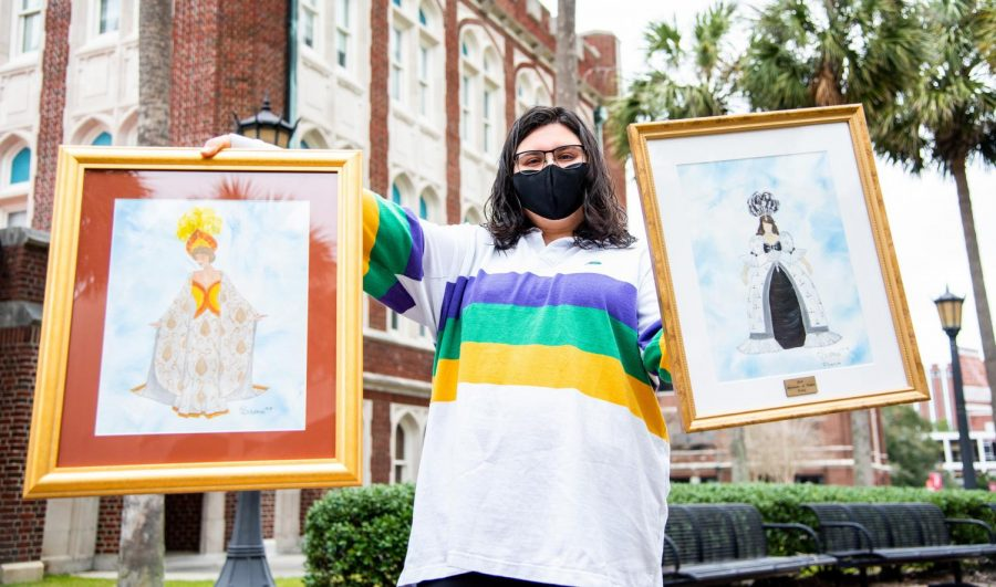 Krewe member Bushra Ahmad holds paintings of Mardi Gras costumes.
