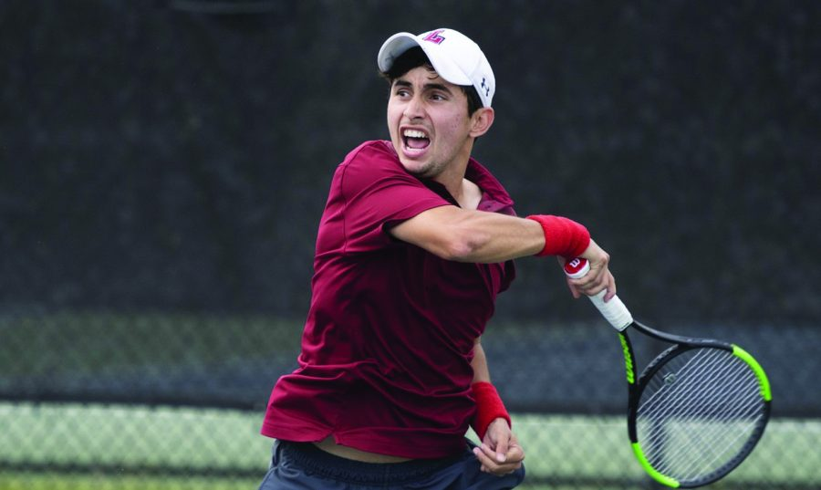 A Loyola tennis player swings his racket.
