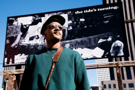 Troy Pierre II poses in front of a billboard featuring his work The Tides Turning.