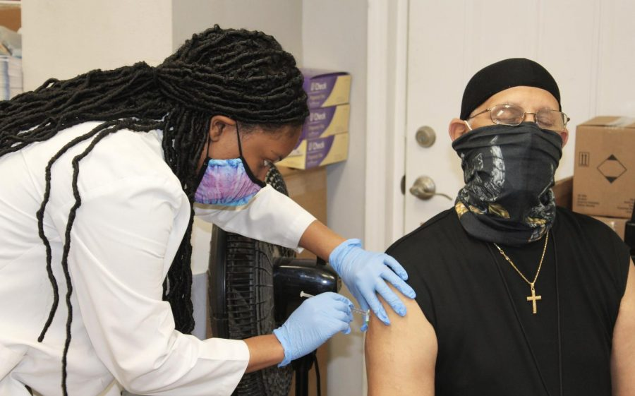 Fourth year pharmacy student Tiffani Collins innoculates Wilfred Griffin, Jr. with his second dose of the COVID-19 vaccine at Crescent City Pharmacy Feb. 18, 2020. A supply shortage set the clinic