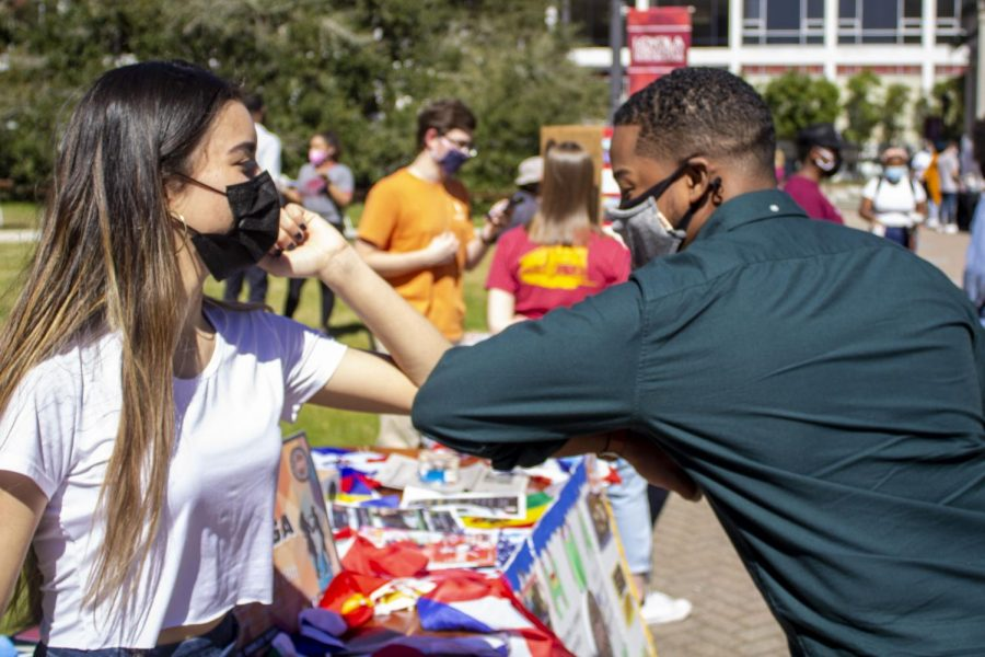 SGA President Freedom Richardson elbow bumps HMA member Maryann Herrera at a student organization fair. Richardson said his life is motivated by service. Photo credit: Madeline Taliancich