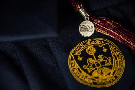 A graduation tassel lays across a gown decked out in Loyola