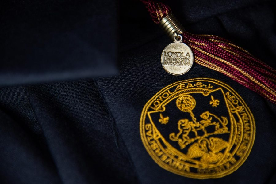 A graduation tassel lays across a gown decked out in Loyola's emblem. Loyola has announced its official graduation plans for the class of 2021.