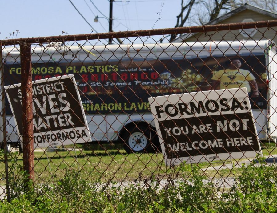 Signs and a trailer from RISE St. James sit in front of a house. The environmental group has been protesting the construction of 14-plant chemical complex Formosa plastics. Photo credit: Rae Walberg