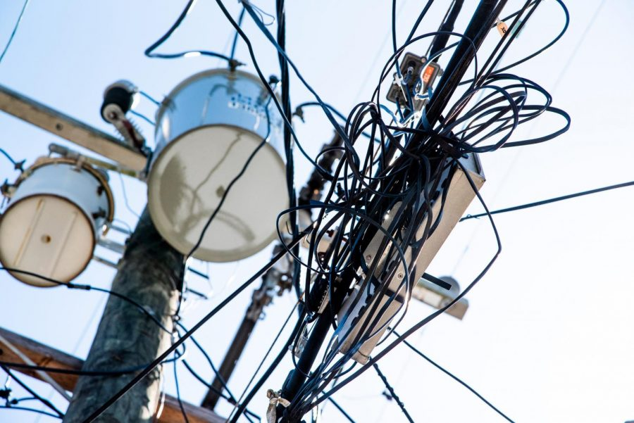 A tangled bunch of wires hangs from a pole in Carrollton. Recently, many Entergy customers have reported rising costs of electric bills. Photo credit: Michael Bauer