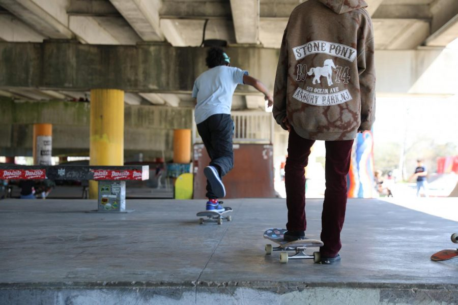 One+skater+pushes+off+as+another+watches+on+at+Parisite+DIY+Skatepark.+Skate+parks+serve+as+a+hub+for+people+to+get+together+and+practice+their+tricks+and+skills.+Photo+credit%3A+Hannah+Renton