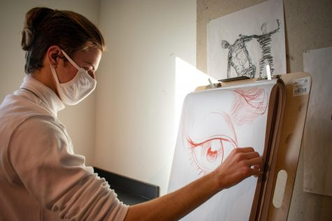 A studio arts major draws in Monroe Hall.
