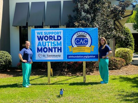 Sunny McDaniel and Dr. McCall McDaniel stand in front of a sign promoting World Autism Month and autism awareness.