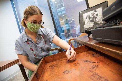 Mass communication senior Rose Wagner signs a desk in the offices of The Maroon. As outgoing editor-in-chief, Wagner joined previous editors-in-chief in signing the desk at the end of her time leading the newsroom.
