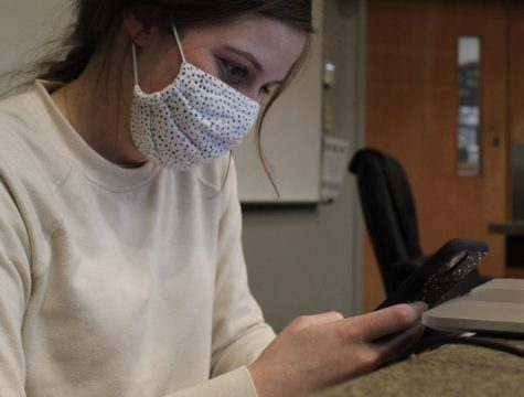 Loyola first year law student Bridget Wallis scrolls through her classs GroupMe group message on her iPhone April 27. The group message has erupted into political debates since last semester, leading to student conduct hearings and mediations. Photo credit: Gabriella Killett