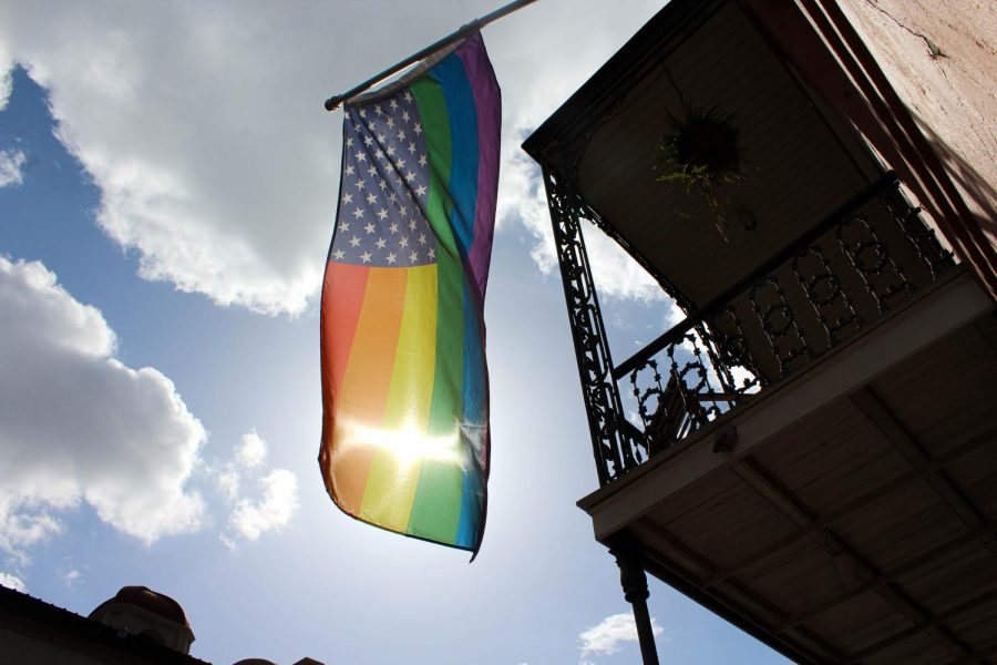 The sun shines through a pride flag hanging from a balcony.
