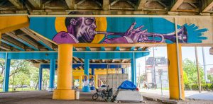 An image under interstate 10 within the treme with a colorful mural on the bridge. Underneath the mural, a tent is located.
