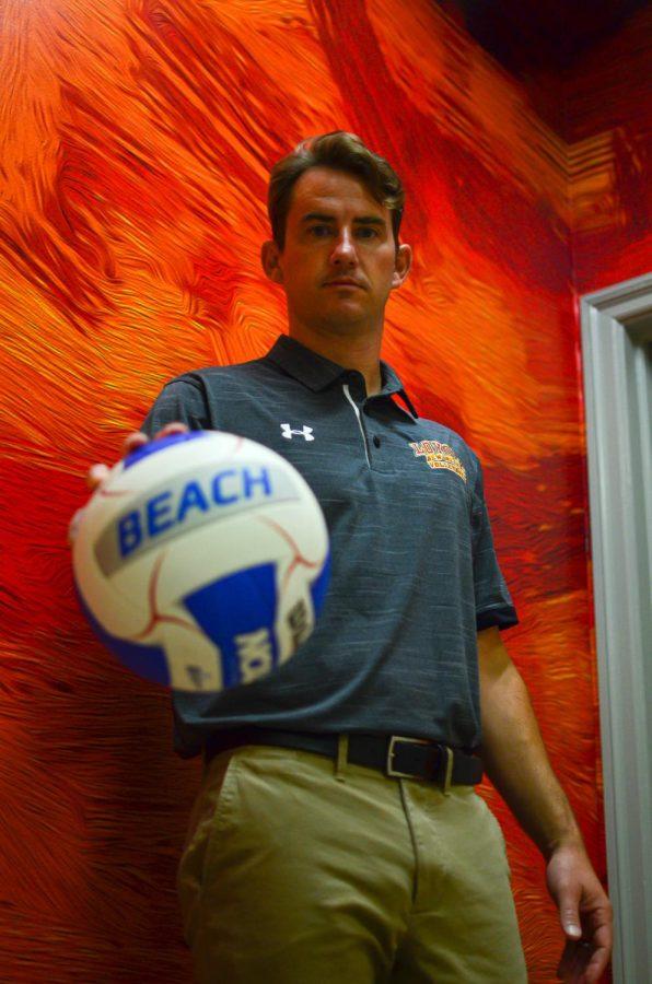 Head Coach Robert Pitre presents a beach volleyball on Tuesday Sept. 21
