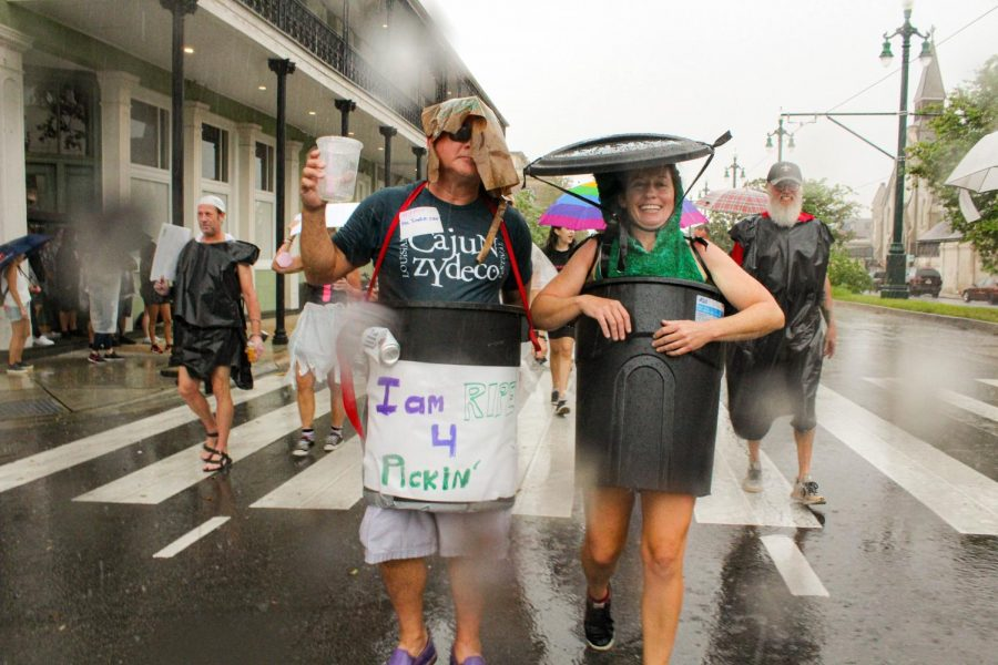 Two New Orleans residents walk in the trash parade wearing trash cans