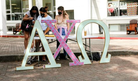 Stephanie Oblena, sophomore environmental studies major, and Nicole Devine, sophomore international business major, talk to a student about sorority events while tabling  for Alpha Chi Omega on Wednesday, Oct. 20, 2021.